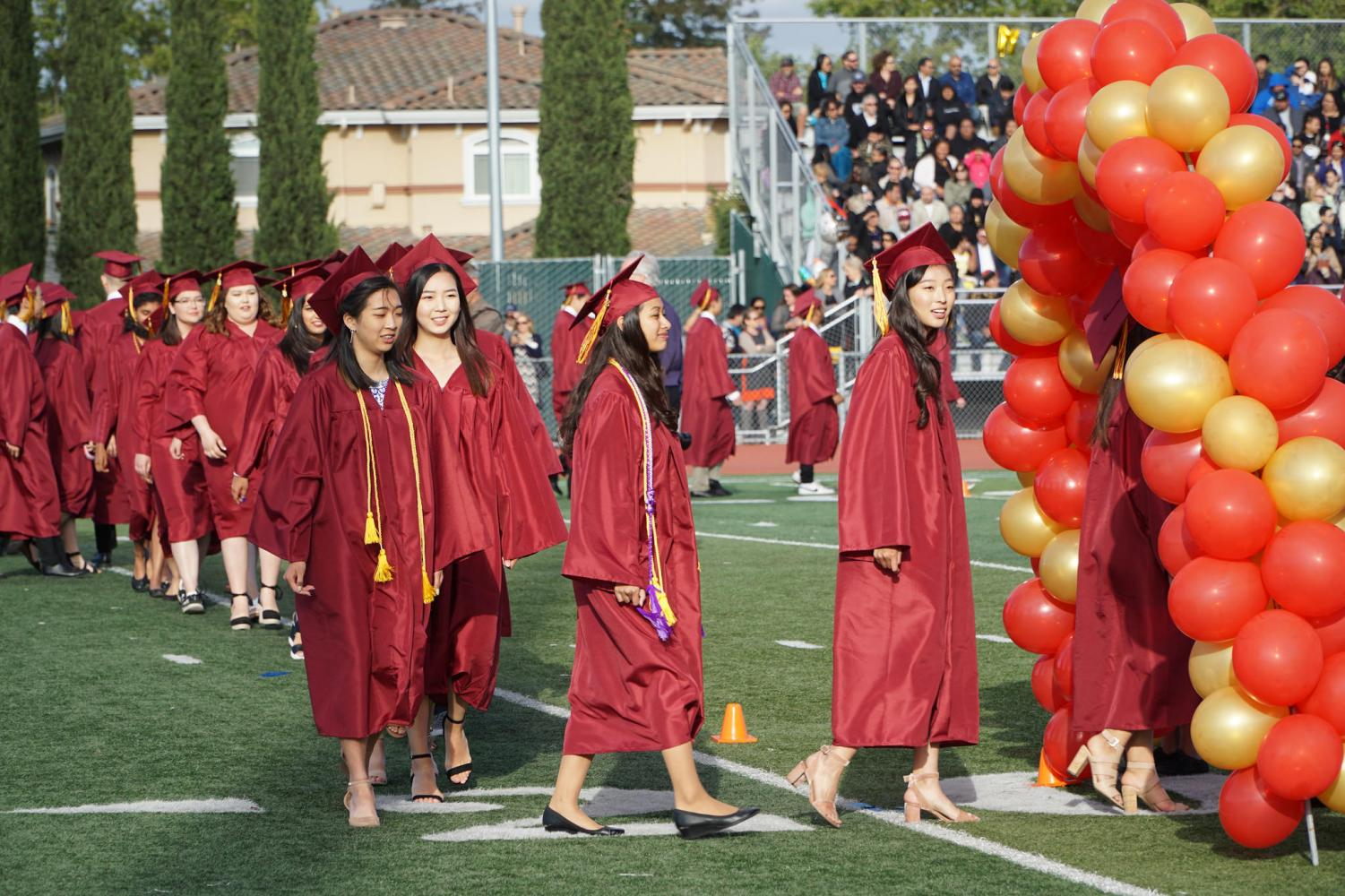Graduates walk through balloon arch prior to taking their seat for the ceremony.
